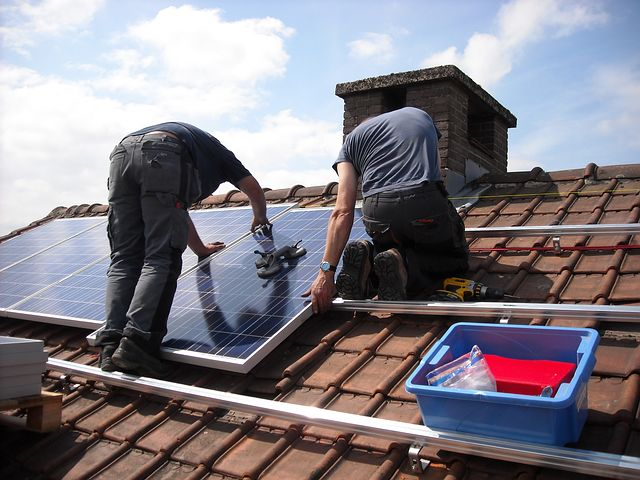 two men connecting solar panels to an SMA sunny boy inverter